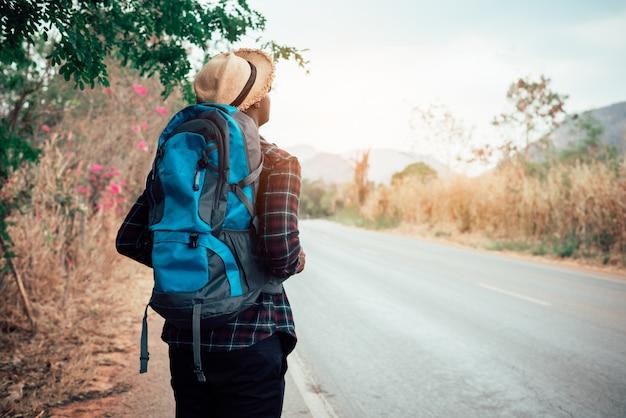 高速道路を歩いてバックパックを運ぶアフリカ人旅行者