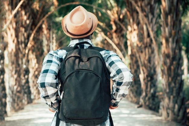 African man traveler carrying backpack walking through the park