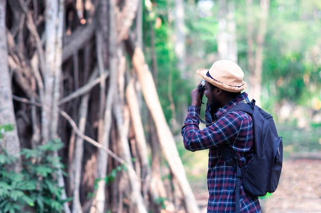 African man traveler explorer with photo camera in forest.