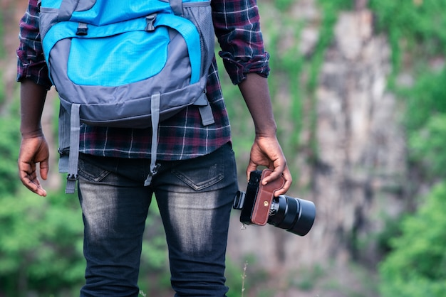 African man traveler holding camera with backpack