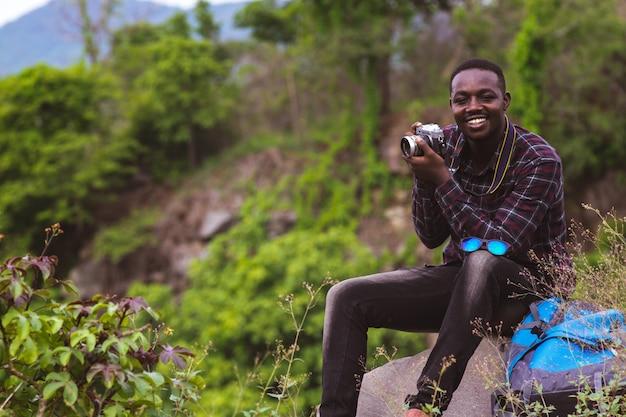 山の頂上で写真を撮るバックパックを持つアフリカ人旅行者