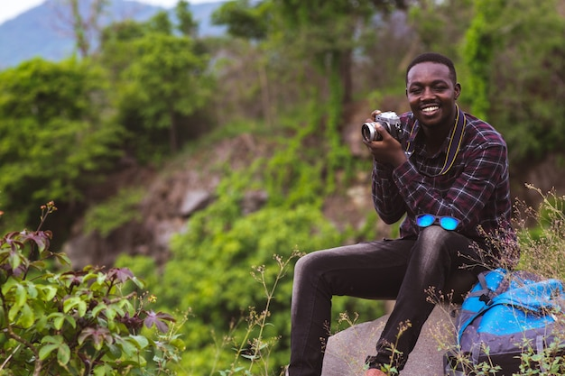 African man traveler with backpack taking a photo on the top of mountains