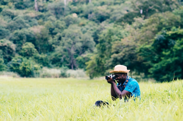 African man travelers take photo and smile happily among green meadows.