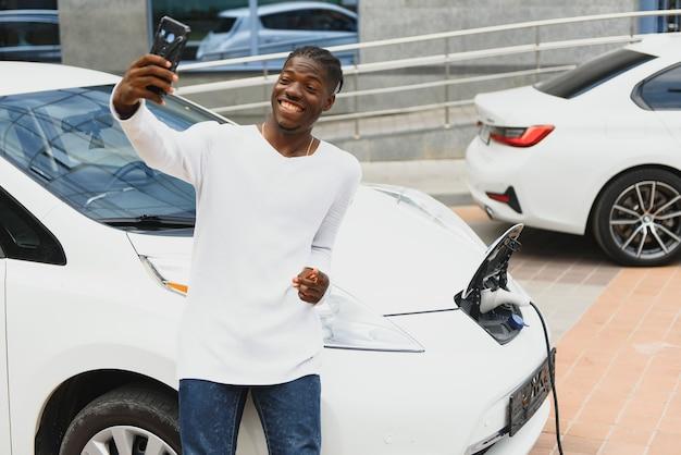 Африканский мужчина использует смартфон во время ожидания, а источник питания подключается к электромобилям для зарядки аккумулятора в машине