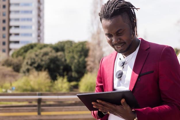 街の屋外でタブレットを使用しているアフリカ人