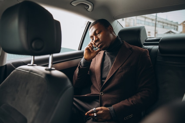 African man using smartphone while sitting on backseat in car.