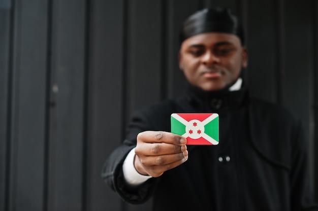 アフリカ人男性は黒いduragを身に着けてブルンジの旗を手元に孤立した暗い壁を保持します。