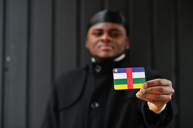 アフリカ人男性は黒いduragを身に着けて中央アフリカ共和国の旗を手元に孤立した暗い壁を保持します。