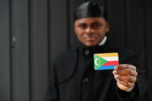 アフリカ人男性は黒いデュラグを身に着けてコモロの旗を手元に孤立した暗い壁を保持します。