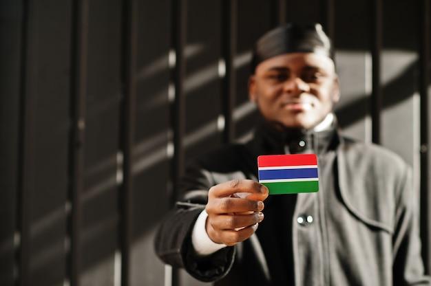 아프리카 남자 착용 검은 durag 손에 고립 된 어두운 벽에 감비아 깃발을 개최.