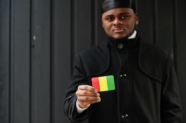 アフリカ人男性は黒いduragを身に着けてギニアの旗を手に持って孤立した暗い壁。