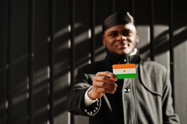 アフリカ人男性は黒いduragを身に着けて、手元にニジェールの旗を掲げ、暗い壁を隔離しました。