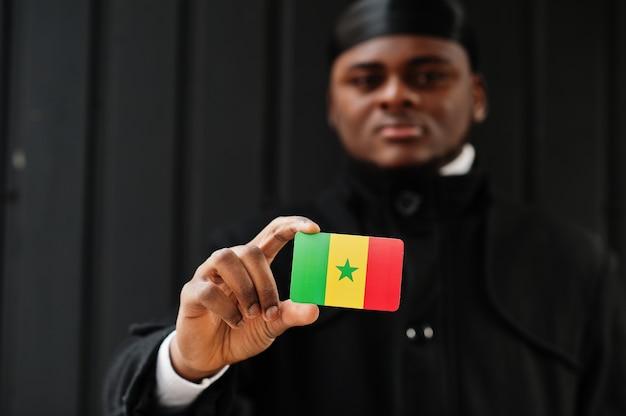 アフリカ人男性は黒いduragを身に着けてセネガルの旗を手に持って孤立した暗い壁