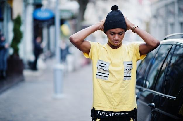 アフリカの男性が黒い帽子をかぶってビジネス車に対して屋外ポーズ。