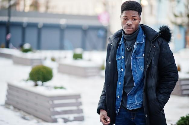 アフリカの男は屋外の寒い冬の天候でジャケットを着用しました。