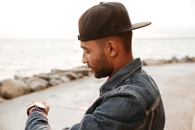 ビーチを歩いて時計を見ているキャップを身に着けているアフリカ人。