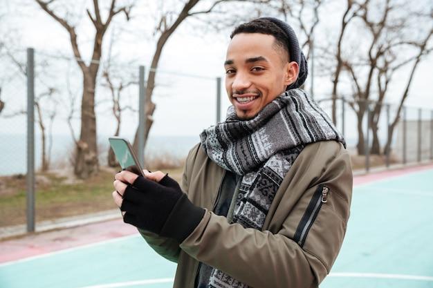 Шляпа и шарф африканского человека нося беседуя по телефону.