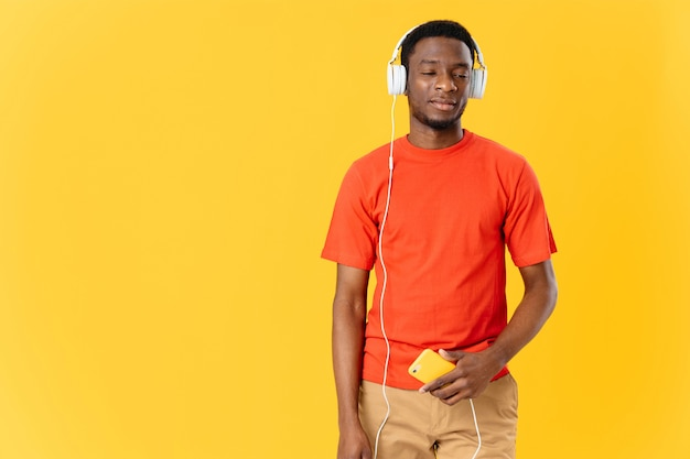African man wearing headphones listening to music technology yellow background