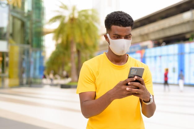 African man wearing yellow t-shirt and face mask to protect from covid-19 coronavirus outdoors in city while using mobile phone