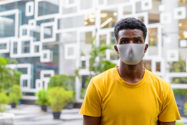 African man wearing yellow t-shirt and face mask to protect from covid-19 coronavirus outdoors in city