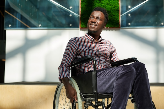 African man in wheelchair looking away and smiling at modern office