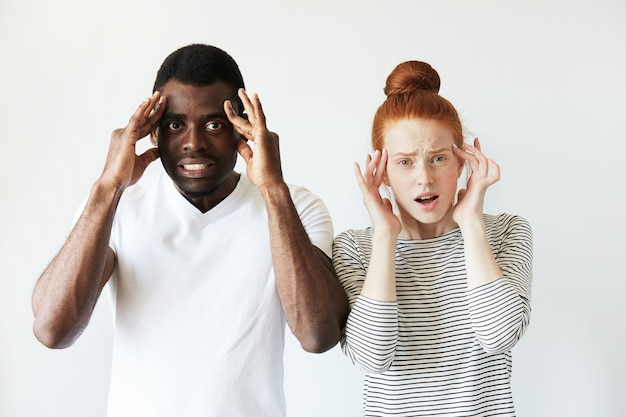 African man in white t-shirt and redhead caucasian woman in striped top