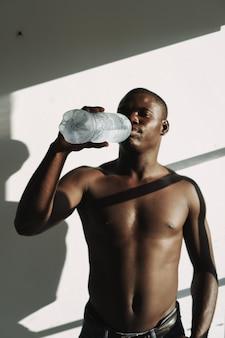 펌핑된 몸통을 가진 아프리카 남자는 밝은 배경 방에 있는 병에서 물을 마신다