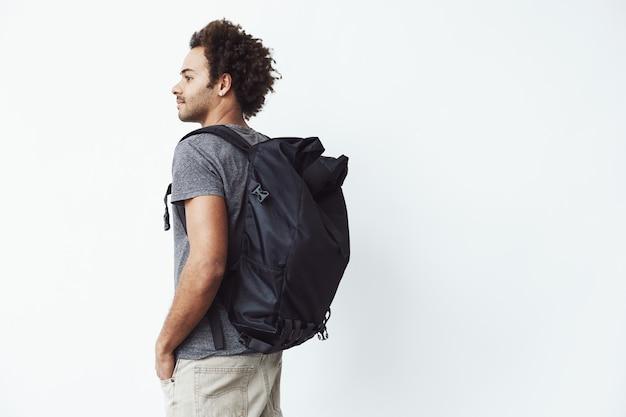側を見てカメラに戻って立っているバックパックを持つアフリカ人。