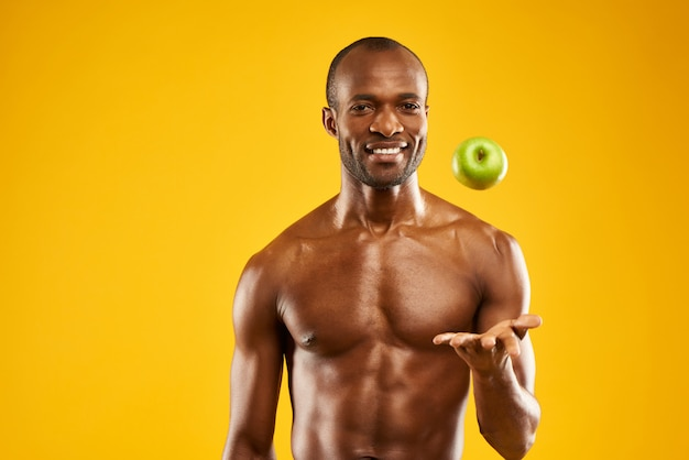 African man with bare torso tosses up an apple into air.
