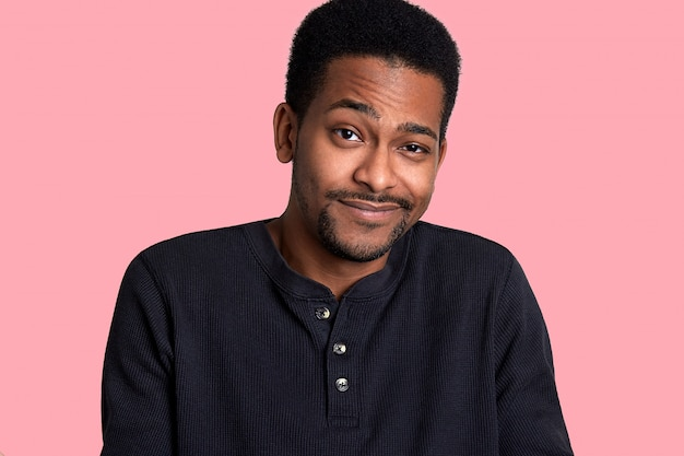African man with beard and mustache crews his eyes and smiles, male looks shy. model stands isolated on pink blackground. young guy wears black shirt. people concept.