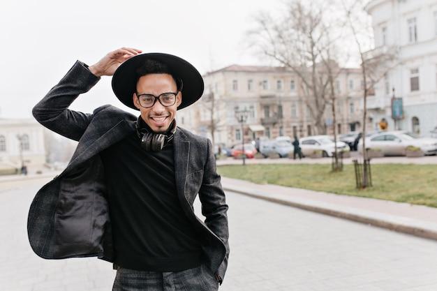 ぼやけた街でポーズをとって自信を持って笑顔のアフリカ人。通りで笑っているポジティブな背の高いムラートの男の屋外写真。