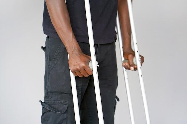 松葉杖でアフリカ人。閉じる。側面図