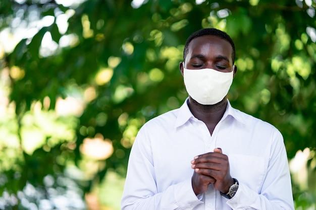 Африканский мужчина в маске молится о борьбе с эпидемией коронавируса