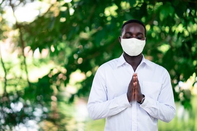 コロナウイルスの流行と戦うために祈っているフェイスマスクを持つアフリカ人