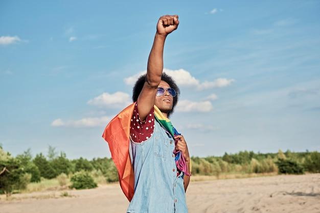 Африканский мужчина с радужным флагом на открытом воздухе