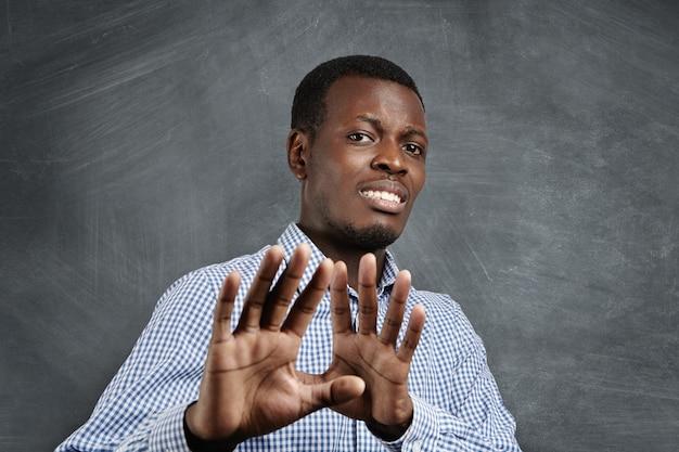 顔を怖がらせた表情で、誰かから身を守ろうとするかのように手のひらで恐ろしい身振りをするアフリカ人。彼の手で身振りで示す恐怖の浅黒い肌の男