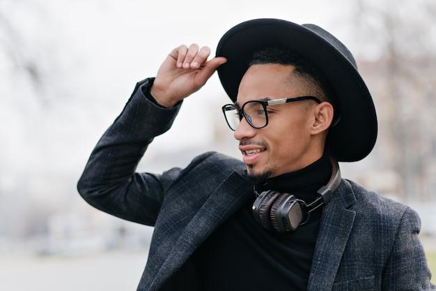 꿈꾸는듯한 얼굴 표정으로 거리에서 찾고 짧은 머리를 가진 아프리카 남자. 도시에서 주말을 즐기는 흑인 남자의 야외 초상화.