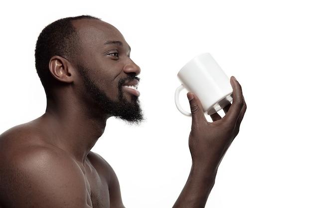 차 또는 커피, 흰색 스튜디오 배경에 고립의 흰색 컵 아프리카 남자. 젊은 벌거 벗은 행복한 아프리카 남자의 미니멀리즘 스타일의 초상화를 닫습니다