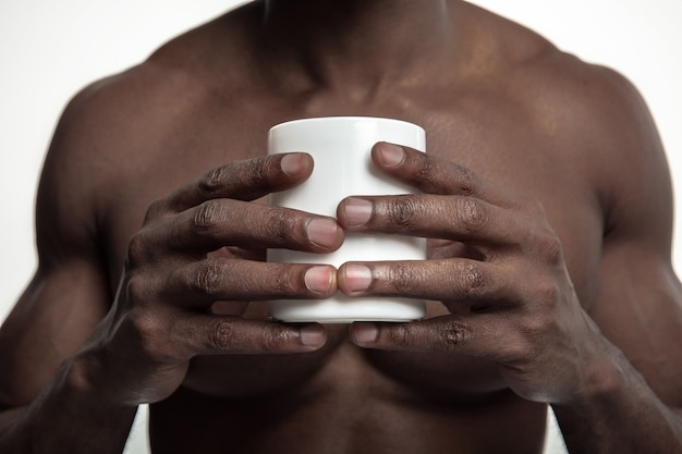白いスタジオで隔離の白いお茶やコーヒーとアフリカの男。