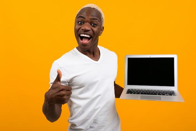 흰 머리를 가진 아프리카 사람이 노란색 배경에 조롱으로 노트북 화면을 앞으로 들고 웃고
