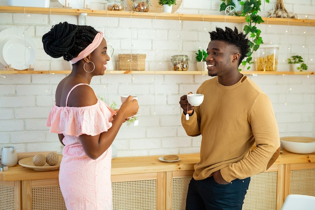 African man and woman in the kitchen drinking tea together