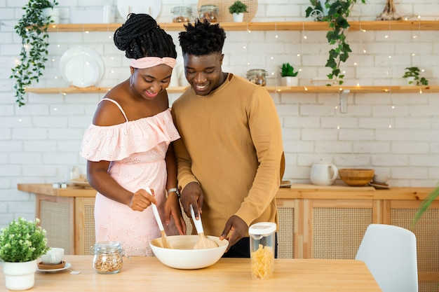 African man and woman in the kitchen preparing food together