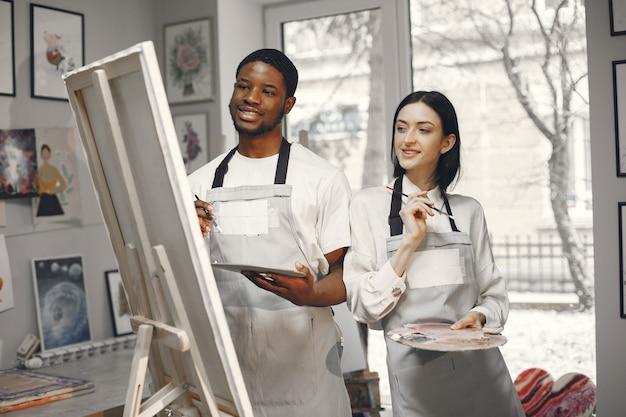 Uomo africano e una donna nella classe di pittura disegno su un cavalletto.