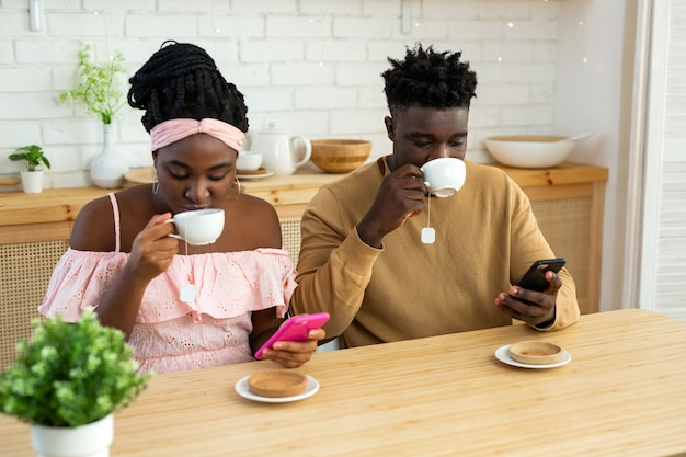 African man and woman sitting at the table in the kitchen with mobile phones