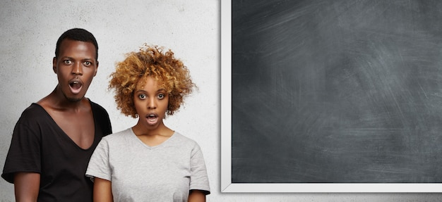 African man and woman standing close to each other at blank chalkboard with copy space for your text or promotional content, looking surprised and shocked, opening mouths widely in full disbelief