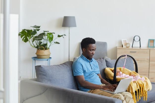 Африканский мужчина работает в сети на своем ноутбуке, сидя на диване со своим ребенком