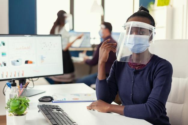 コロアンウイルスに対してフェイスマスクを着用している同僚と一緒にオフィスにいるアフリカのマネージャー。世界的大流行の際の社会的距離を尊重する金融会社で働く多民族のビジネスチーム。