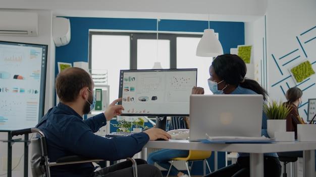 新しい通常のオフィスで無効な従業員と一緒に働いているフェイスマスクを持つアフリカのマネージャー