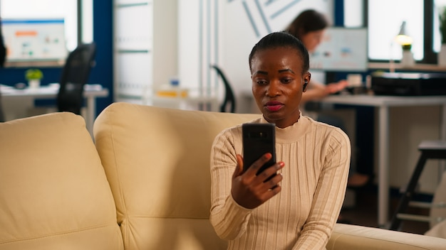 African manager woman discussing with remote colleagues on video call holding smartphone using headphones sitting on couch in business modern office. diverse coworkers planning new financial project