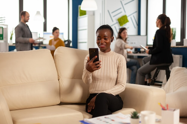 African manager woman discussing with remote colleagues on video call holding smartphone using headphones sitting on couch in business modern office